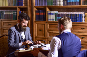 Man in suit or journalist with friend in library.
