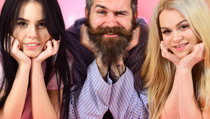 Man with beard and mustache, blonde and brunette girls. Girls with bearded macho, pink background. Best friends concept. Threesome on smiling faces lay near balloons, cheerful company, close up.