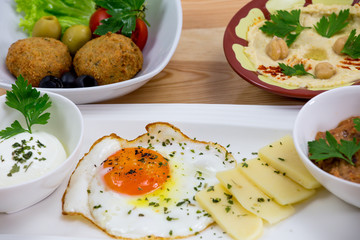 Traditional Arabic breakfast, lettuce, eggs, cheese, olives, and decorative vegetables, served on a plate, restaurant, service