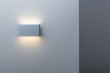A glowing modern aluminum led lamp on the gray wall. Free space and a darker stripe