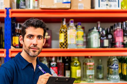 Hombrejoven con barba  en almacén sujetando carpeta sonriendo con botellas de fondo