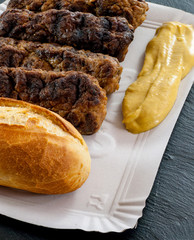 Fototapete - Delicious grilled minced meat rolls mici ori mititei traditional romanian and balkan dish served with mustard cardboard tradition fast food concept