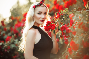 Portrait of beautiful happy blonde girl in bush of red roses