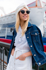 Stylish blonde woman posing on background of yacht club outdoors in summer city street at sunset time wearing white shorts and shirt with black glasses. Vacation mood, travel