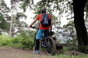 Mountainbiker macht Pause an einer Bank