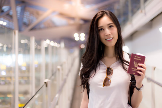 Charming beautiful woman go to foreign country for working. Attractive girl show thai passport. Pretty asia woman feel happy because she get good job, good salary. She arrives to airport early morning