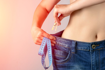 lost weight woman in her old big jeans, fixes her jeans with a clothespin. A healthy body after a diet, a sport.  grow thin by the summer