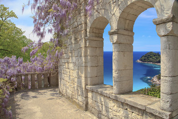 Beautiful view of the loggia and on the sea, a loggia of natural stone the masonry with arched windows ,  blossoming Wisteria on the loggia