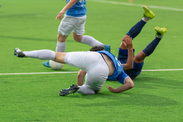 Football players tumbling on the football field. Falling players in the fight for the ball