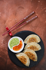 Stone slate tray with roasted potstickers, flat-lay on a fire warm rusty metal background, vertical shot with space