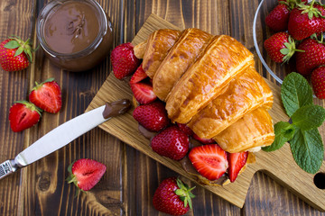 Croissant  with chocolate cream  and strawberry on the  wooden  cutting board.Top view.