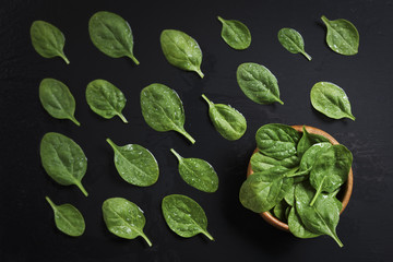 Wooden bowl with fresh spinach on natural black slate stone background