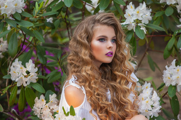 .Portrait of a girl in blooming gardens, white rhododendron. Long hair and beautiful makeup.