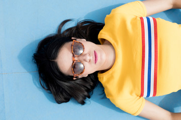 Woman in sportswear and sunglasses lying on blue