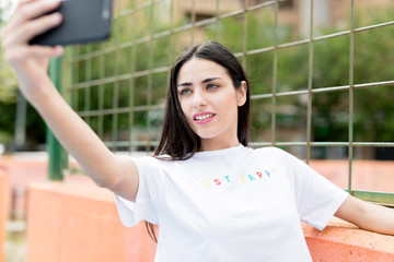 Young slim woman standing and making selfie