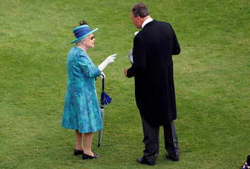 Britain's Queen Elizabeth II speaks to a member of stuff as she hosts a Garden Party at Buckingham Palace in London