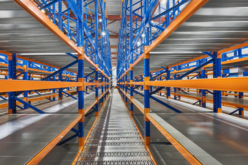 Empty shelves in new distribution warehouse. Metal equipment for storage, racks blue orange, pallet racking system