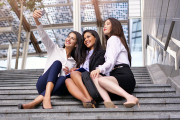 Business women of different ethnic backgrounds dressed in suits and suits, they take a picture in which they smile and they are all happy. Concept of: internationality and technology, social networks