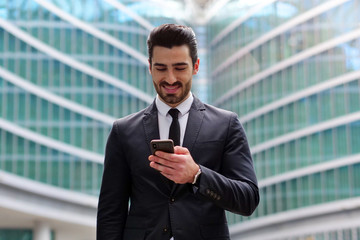 An business man in a suit and tie is happy and smiling while sending messages, working emails or calling using the phone. Concept of: technnology, network, success.