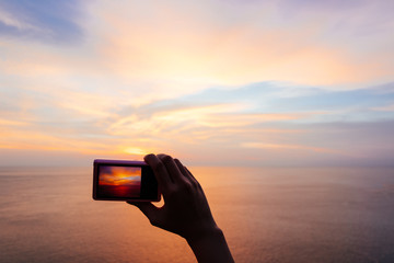 Woman hand holding digital camera and taking photo twilight sunset sky over sea.