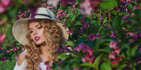 A beautiful young girl on a sunny summer day, wearing a hat. Against the backdrop of a blooming garden. Flowers are pink. Beauty hairstyles curls and makeup.