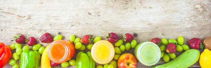 freshly squeezed fruit juice, smoothies yellow orange green blue banana lemon apple orange kiwi grape strawberry on a dark wooden background Copy space. Flat lay Banner concept
