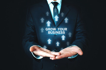Man holding Grow Your Business words with growth arrows.