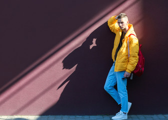 fashion guy standing near a viola wall in yellow clothes