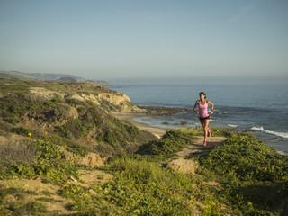USA, California, Newport Beach, Woman running along cliff