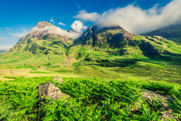 Green valley in mountains of Glencoe at sunrise, Scotland