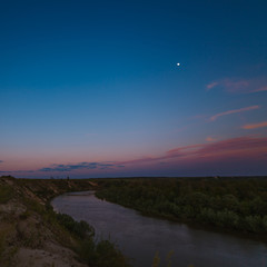 Night sky with a bright moon over the river. Photographed on a long exposure to the light of the moon.