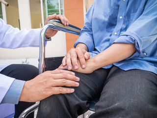 Doctor hold hand patient on wheelchair.