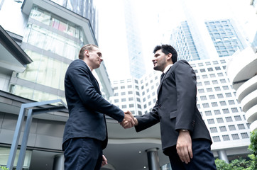 Two Handsome business man shaking hands outside modern office building. Dealing and partnership concepts.