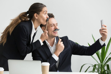 Friendly colleagues in suits having fun grimacing holding fake mustache taking picture on smartphone in office, happy coworkers making funny faces laughing at phone camera, silly selfie concept