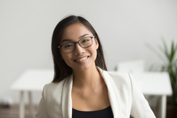 Smiling asian woman in glasses for vision correction looking at camera, happy friendly chinese student or employee posing in office, millennial japanese woman professional head shot portrait Wall mural