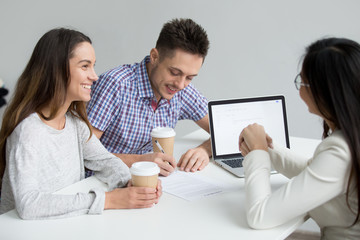 Happy young couple signing contract taking loan at meeting with bank worker, smiling customers making mortgage investment deal, clients buying insurance services putting signature on legal document