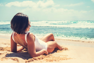 Woamn takes a sun bath on tropical beach