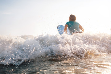 Woman on surfboard swims over the wave