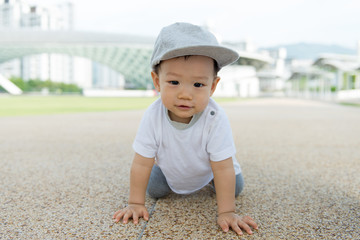Beautiful baby boy crawling outdoor in park, learn to walk