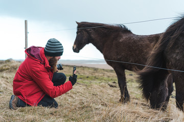 Man taking pictures of Icelandic horse