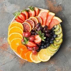 Assortment of cut fruits in rainbow colours oranges grapes mango strawberries kiwis blueberries grapefruit on the grey concrete table, copy space, top view, square, selective focus
