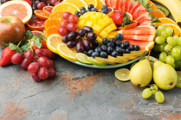 Healthy fruits background in rainbow colours oranges apples grapes pears mango strawberries kiwis on the grey concrete table, copy space, selective focus