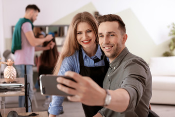 Hairdresser with happy client taking selfie in beauty salon