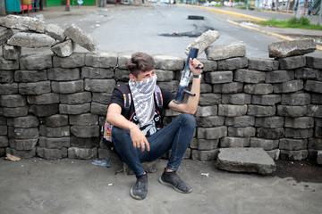 A demonstrator takes a break behind a barricade during a protest against Nicaraguan President Daniel Ortega's government in Managua