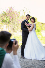 Professional photographer taking photo of wedding couple, outdoors