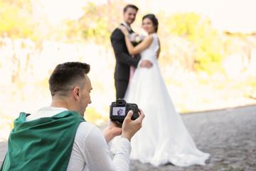 Professional photographer taking photo of wedding couple, outdoors