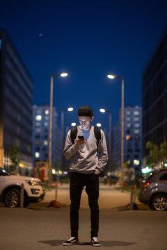 The man phone on the street. Evening night time. Street lights. Telephoto lens shot