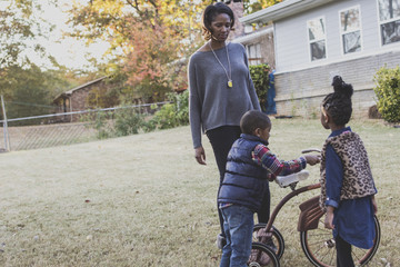 Fototapete - Family standing in yard with tricycle