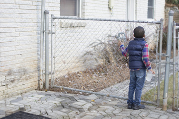 Rear view of a boy standing near chainlink gate