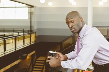 Portrait of businessman having coffee in office